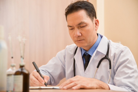 Asian Senior male doctor is thinking about result of examination of his patients. Writing something on clipboard, prescription, paper work,patient check list paper or application form.