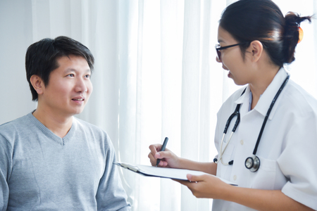 Asian Female Doctor examining and taking note on checklist paper with male patients in medical room.