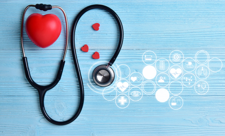 Red hearts with stethoscope on blue wooden background. Copy space. Valentines day. Archivio Fotografico