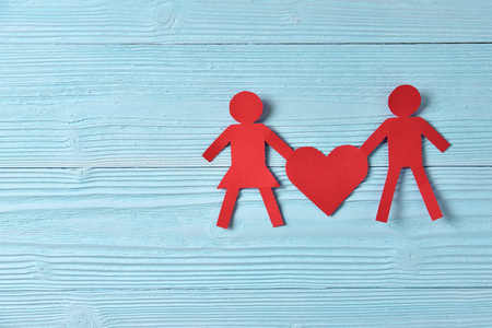 Red paper people holding heart on blue wooden background. Copy space.