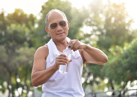Asian senior male wear sunglasses holding bottle of water for drinking while exercise at park outdoor background. Banco de Imagens