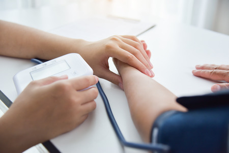 Asian Female doctor checking a senior woman patient pulse. Health care.