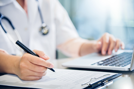Close up on hands. Asian female doctor is using laptop and writing something on clipboard, prescription, paperwork,patient checklist paper or application form at a hospital.