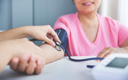 Asian Female doctor measuring blood pressure of a senior woman patient. Stethoscope. Health care.