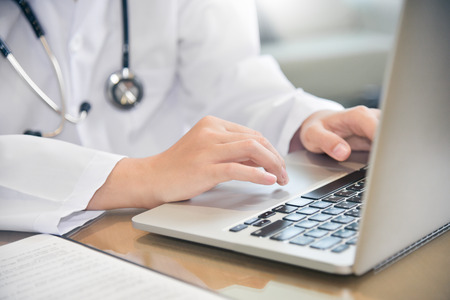 Close up on hands. Female Doctor working with laptop on wooden desk at a hospital. Medical and health care concept. Stethoscope.