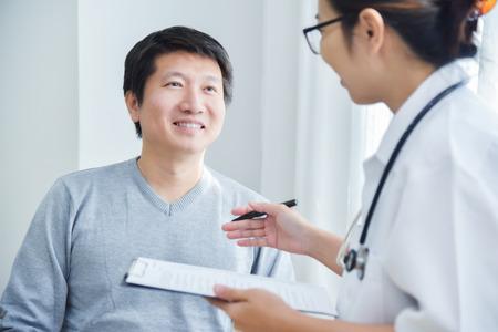 Asiatischer weiblicher Doktor, der an Checklistenpapier mit männlichen Patienten im medizinischen Raum überprüft und sich nimmt.
