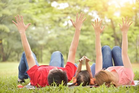 Happy young Asian family with their daughter are lying and raised hands up on green grass in nature at park outdoor. Holiday and Having fun. Reklamní fotografie