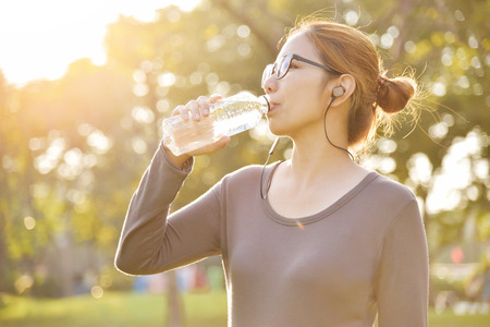 Young Asian female  in Grey sportswear is resting and drinking water while exercise at park. Woman listening to the music with earphones at outdoors on morning.  Health care concept.  Sunset and Sunlight. Copy space. Stockfoto