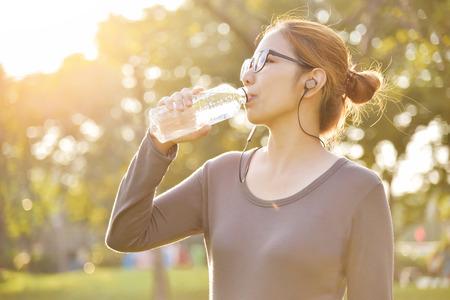 Junge asiatische Frau in grauer Sportkleidung ruht und Trinkwasser während der Übung im Park . Frau hört Musik mit Kopfhörern im Freien auf Sonnenuntergang . Im Freien auf Hintergrund . Mann und kopieren . Platz kopieren Standard-Bild - 94927235