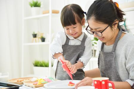Feliz niño Asiático y joven madre decorar galletas en la cocina.