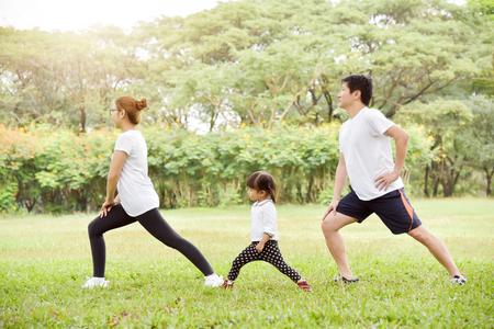 Familia asiática feliz con su hija en entrenamiento de camisa blanca en el parque. La gente está calentando y estirando los brazos al aire libre en la mañana. Concepto de salud. Copia espacio Ejercicio