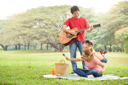 Happy young Asian family with their daughter having fun in nature at park outdoor.