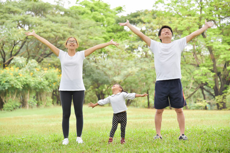 Happy Asian family with their daughter in white shirt workout at the park. People are warming up and stretching their arms at outdoors on morning. Health care concept.  Copy space. Exercising.