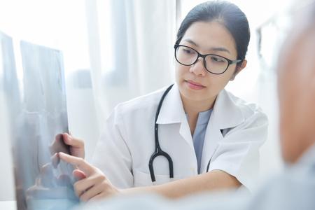 Las doctoras asiáticas jovenes usan los vidrios que examinan la película de radiografía del paciente masculino mayor.