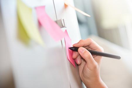 Vrouwelijke hand die op post-itnota's schrijft. Notitie op de muur. Kleurrijk. Stockfoto