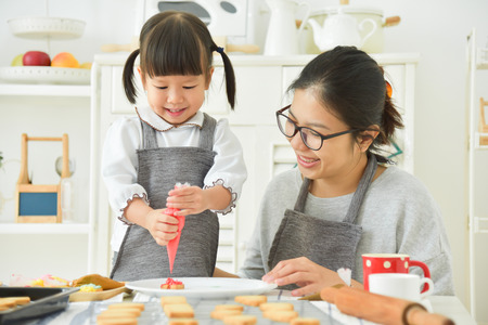 Happy Asian Kid and young mother decorating cookies in the kitchen. Stock fotó - 95620994