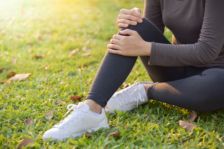 Healthy Woman in grey sportswear Injured on her knee from exercise at park outdoor. Asian female sitting and resting on grass. Copy space.