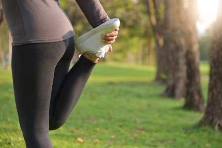 Asian female workout at the park. Young woman is warming up and stretching her legs at outdoors on morning. Health care and sport concept. Exercising.