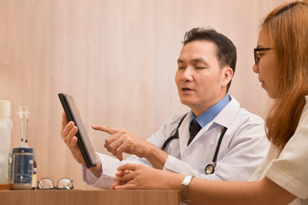 Close up Asian senior male Doctor using digital tablet computer and discussing with female doctor. Medical and health care concept.