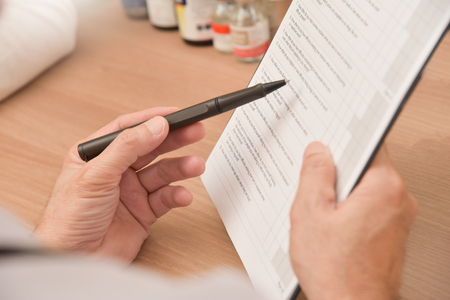 Close up on hands. Asian senior male doctor is holding a clipboard, prescription, paper work, patient check list paper or application form.