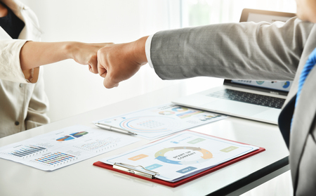 Businessman and businesswoman making a fist bump together after good deal. Business success and teamwork concept. Contract, Negotiation, Partnership. Standard-Bild