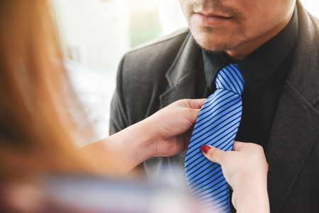 Asian young couple getting dressed. Hands holding on a blue necktie of beard male.