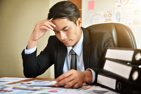 Stressed Young Asian Businessman having headache while he work overtime. Chest pain.