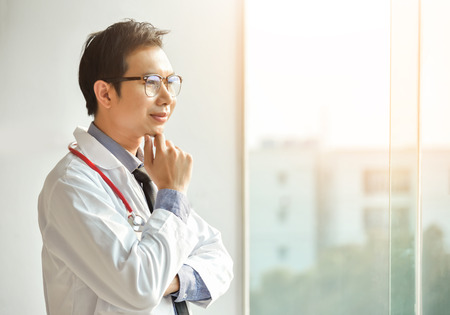 Portrait of Young Asian male Doctor is posing with arms crossed and looking through the window. copy space. Thinking.