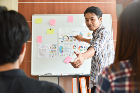 Confident Asian Creative male Designer making a new business presentation project to a group. Foto de archivo