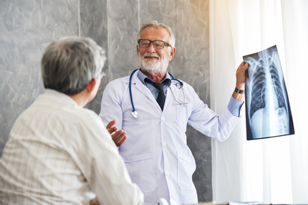 Senior Male doctor and Asian patient are examining x-ray film in a medical room together.