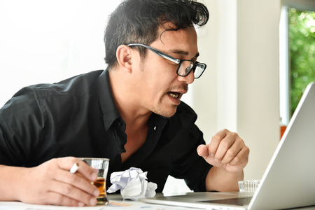 Alcohol addicted businessman is holding whiskey glass while working with laptop. Sad depressed patient male adult having troubles. Asian Drunk man with Alcoholism.
