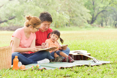 Happy young Asian family with their daughter Reading a book. People having fun in nature at park outdoor. Stock Photo