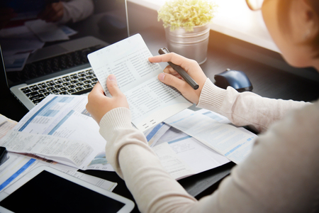 Aziatische vrouw die aan het boek van de besparingsrekening kijken en haar maandelijkse uitgaven met calculator berekenen. Schuld.