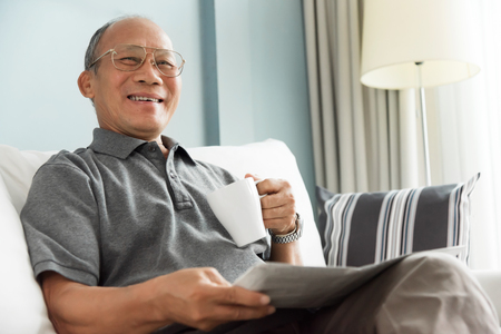 Happy Asian senior man smiling and drinking hot coffee while reading newspaper at his house. Relaxed, Free time, Smiling, Retirement.