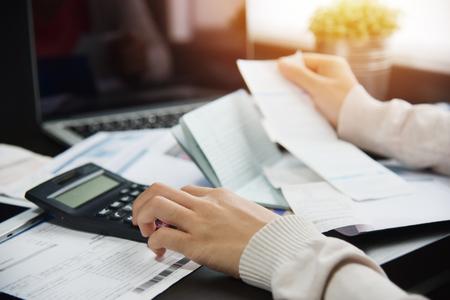 Sluit omhoog van vrouwenhand die haar maandelijkse uitgaven met calculator berekenen. Schuld. Stockfoto