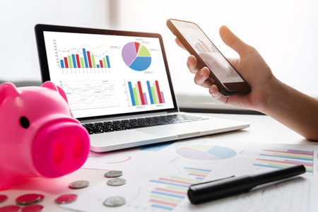 Close up of woman hands holding cell phone. Pink Piggy Bank, Laptop, Calculator, business chart and graph document on desk. Debt.