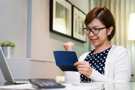 Beautiful Asian female smiling. Happy Young Business woman holding saving account passbook. Successful. Laptop, tablet, calculator on desk at working room. Stock Photo