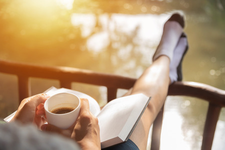 Happy Woman sitting and holding cup of hot coffee while reading book with natural landscape. Enjoying morning. Relax time.