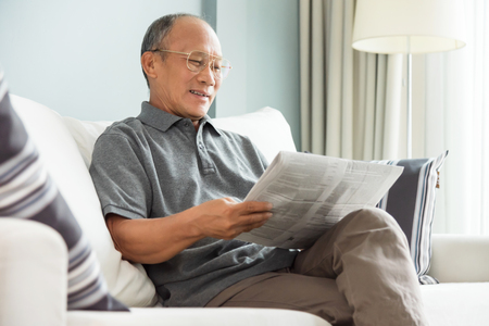 Happy Asian senior man sitting and reading newspaper at his house. Relaxing, Smiling, Retirement. Foto de archivo - 104434577