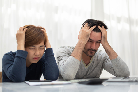 Stressed Young couple calculating their budget for new house.