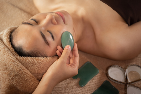 Beautiful Asian female getting Jade Facial Treatment at the Spa Salon. Masseuse hands doing Face Massage. Zdjęcie Seryjne