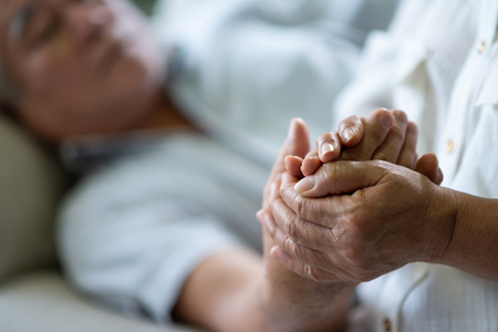 Asian Senior Couple holding hands together. Disease, illness, Comforting.
