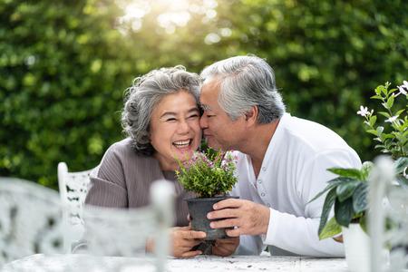 Portrait d'un homme senior asiatique embrassant sa femme. Couple plus âgé bénéficiant de la plantation de fleurs dans le jardin. Retraite.