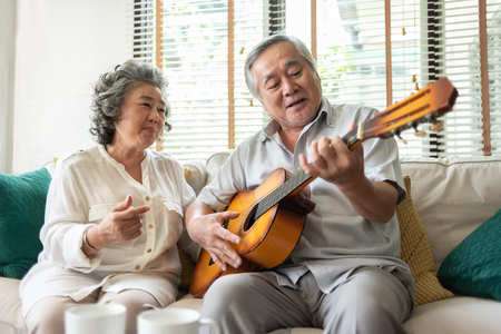 Happy Retirement Older Couple enjoying with singing and guitar together. Having fun. 免版税图像
