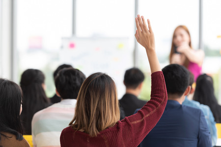 Young student Raising Hand Up in a classroom.