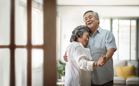 Cheerful Asian Senior couple dancing and smiling at home. Copy space.