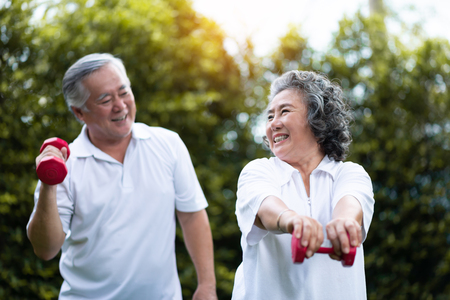 Asian Senior Couple exercising with red dumbbells at the outdoor park togetherness. Smiling Chinese or Thai or Japanese people. Stockfoto