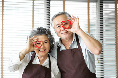 Having Fun with baking. Portrait Asian senior couple wear brown aprons are holding red cookies cutters in heart shape over their eyes. Looking at the camera.