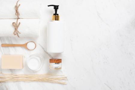 Vista superior de botellas de cosméticos, jabón, cuchara de madera y toalla sobre fondo de mármol blanco. Productos de spa con espacio de copia.