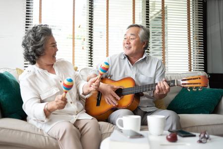 Couple de personnes âgées asiatiques s'amusant à chanter et jouer de la guitare ensemble.